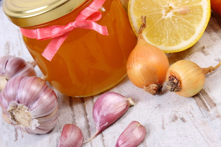 immunity: Fresh organic honey in glass jar, onion, garlic and lemon on old wooden background, healthy nutrition, strengthening immunity and treatment of flu