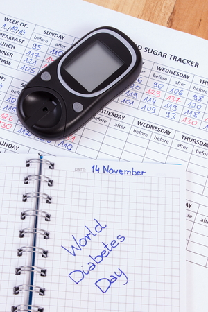 medical fight: World diabetes day written in notebook, medical forms with results of measurement of sugar and glucose meter, symbol of diabetic and fight against diabetes