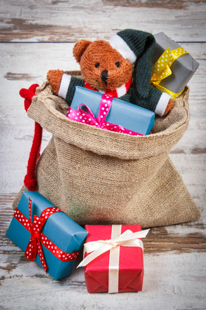 christmas paper: Teddy bear and wrapped colorful gifts for Christmas, birthday, valentines or other celebration in jute bag on old wooden white table Stock Photo