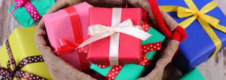 gift bags: Heap of wrapped colorful gifts for Christmas, birthday or other celebration in jute bag lying on old wooden white plank