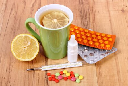 nose drops: Pills, nose drops and hot tea with lemon for colds, treatment of colds, flu and runny Stock Photo