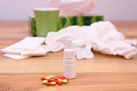 handkerchiefs: Pills and nose drops for colds, used handkerchiefs and hot tea in background, treatment of colds, flu and runny