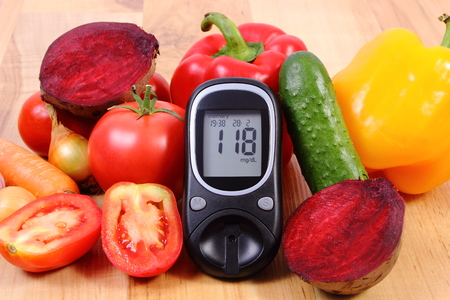 Fresh ripe vetables and glucose meter on wooden table, diabetes, healthy lifestyle and nutrition, result of measurement of sugar