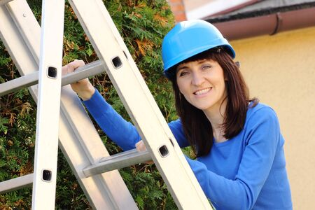 enters: Smiling woman in protective blue helmet climbing on aluminum ladder in garden, enters the ladder, security and protection at work Stock Photo