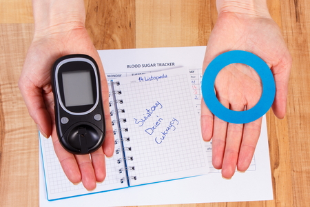 diabetes: Glucose meter and blue circle of paper in hand, polish inscription world diabetes day in notebook, symbol of diabetic and fight against diabetes Stock Photo
