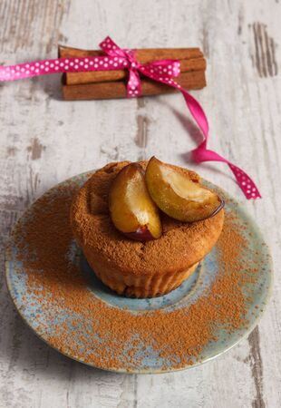 powdery: Homemade fresh baked muffins with plums and powdery cinnamon on plate and cinnamon sticks on old rustic wooden background, delicious dessert Stock Photo