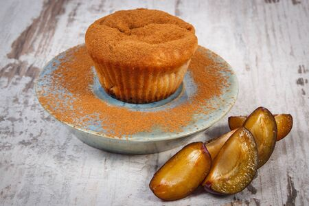 powdery: Homemade fresh baked muffins with plums and powdery cinnamon on plate on old rustic wooden background, delicious dessert Stock Photo