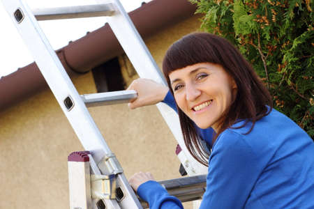 enters: Smiling woman climbing on aluminum ladder in garden, enters the ladder Stock Photo