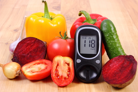 glucometer: Fresh ripe vetables and glucometer on wooden table, diabetes, healthy lifestyle and nutrition, result of measurement of sugar