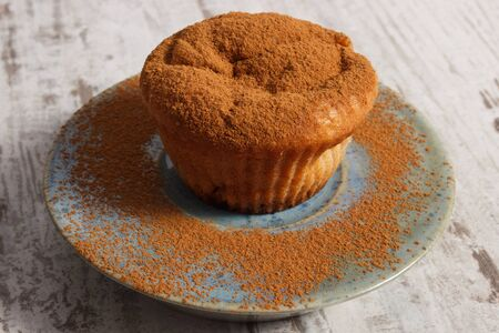 powdery: Homemade fresh baked muffins with powdery cinnamon on plate on old rustic wooden background, delicious dessert Stock Photo