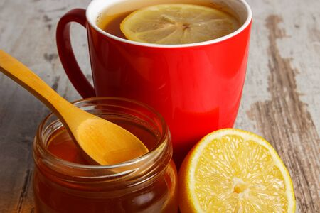 immunity: Fresh lemon, honey in glass jar and cup of hot tea on old wooden white table, healthy food, strengthening immunity and alternative therapy Stock Photo