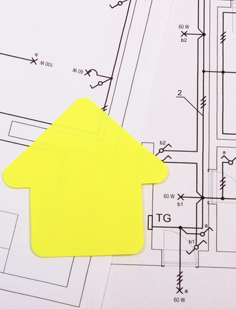 YELLOW: House of yellow paper lying on electrical construction drawing of house, technology and concept of building home