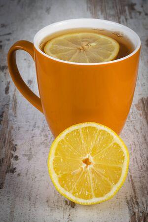inmunidad: Lim�n fresco y una taza de t� caliente con lim�n en la mesa de madera blanca, la nutrici�n saludable, fortalecer la inmunidad y la terapia alternativa