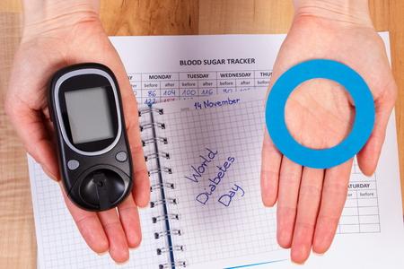 diabetes: Medidor de glucosa y el círculo azul de papel en la mano, el día Mundial de la Diabetes inscripción en el cuaderno, símbolo de la diabetes y la lucha contra la diabetes