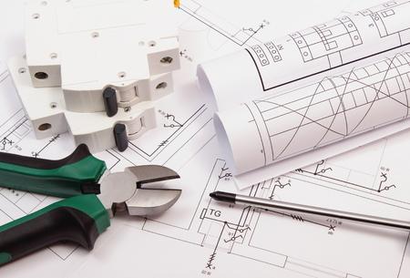 ingenieria elÉctrica: Pinzas de metal, destornillador, fusibles eléctricos y rollos de diagramas de dibujo de construcción eléctrica de la casa, la herramienta de trabajo y la elaboración de trabajos de proyectos de ingeniería, concepto de la construcción de la casa Foto de archivo