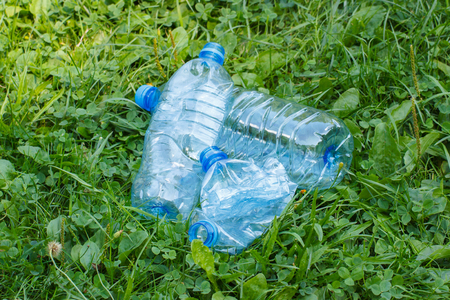 tirar basura: Botellas aplastadas pl�sticas de agua mineral en el c�sped en el parque, el concepto de protecci�n del medio ambiente, basura del medio ambiente