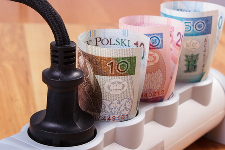 energy costs: Rolls of polish currency money in electrical extension with connected plug, power board, concept of saving money on electricity, energy costs Stock Photo