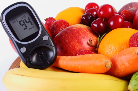 inmunidad: Glucose meter with fresh ripe fruits and vegetables, concept of diabetes, healthy food, nutrition and strengthening immunity. Isolated on white background