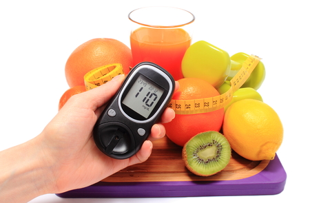 diabetes: Glucometer in hand. fresh fruits, dumbbells for using in fitness, tape measure and glass of juice, concept for diabetes, slimming, healthy nutrition and strengthening immunity