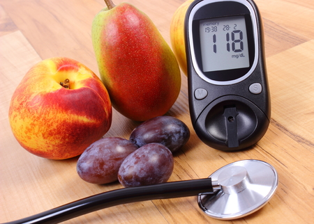 diabetes: Medidor de glucosa con el estetoscopio médico y frutas frescas, el concepto de la diabetes, estilos de vida saludables y la nutrición Foto de archivo