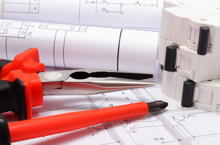 housing project: Rolls of electrical diagrams, electric fuse and work tools lying on construction drawing of house, drawings for the projects engineer jobs