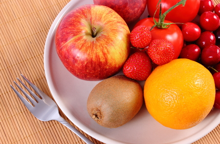 immunity: Fresh ripe fruits and vegetables lying on plate and cutlery on wooden surface, concept of healthy food, nutrition and strengthening immunity