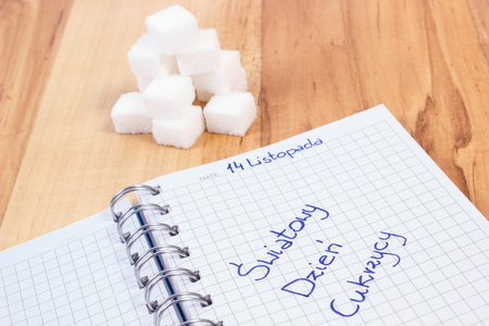 diabetes: Polish inscription World diabetes day in notebook and sugar cubes, symbol of diabetic and fight against diabetes