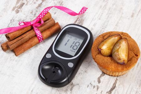 diabetes: Medidor de glucosa, magdalenas con ciruelas y palitos de canela en viejo fondo de madera rústica, el concepto de la diabetes y delicioso postre, resultado de la medición del azúcar Foto de archivo