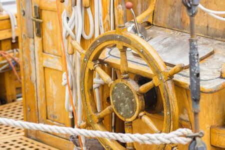 yachting: Yachting, helm of old wooden sailboat in port of sailing, rope, steering wheel, details of yacht Stock Photo