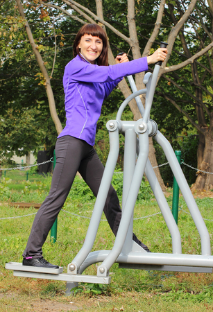lower body: Brunette woman exercising upper and lower body on outdoor gym, concept of healthy and sporty lifestyle