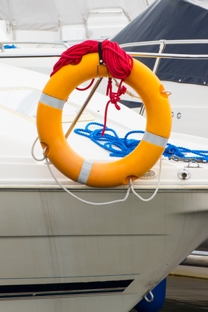 coiled: Yachting blue and red coiled rope with orange lifebuoy on deck of sailboat, part of yacht, safety travel