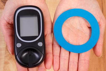 diabetes: Medidor de glucosa y el círculo azul de papel en la mano, símbolo de la diabetes y la lucha contra la diabetes