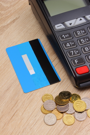 technology transaction: Payment terminal with credit card and polish currency money on wooden desk, credit card reader, paying using credit card or cash, finance and banking concept