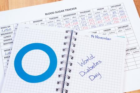 diabetes: D�a de la diabetes del mundo escrito en el cuaderno, c�rculo azul de formularios en papel y m�dicos con los resultados de la medici�n de az�car, s�mbolo de la diabetes y la lucha contra la diabetes