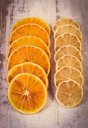 lemon slices: Vintage photo, Slices of fresh dried lemon and orange lying on old rustic wooden background Stock Photo