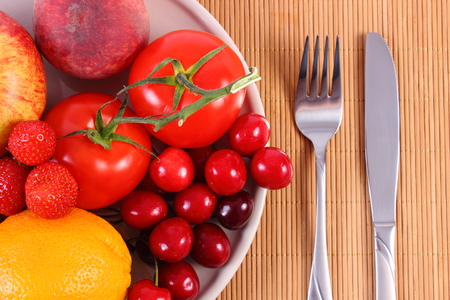 fruit plate: Fresh ripe fruits and vegetables lying on plate and cutlery on wooden surface, concept of healthy food, nutrition and strengthening immunity