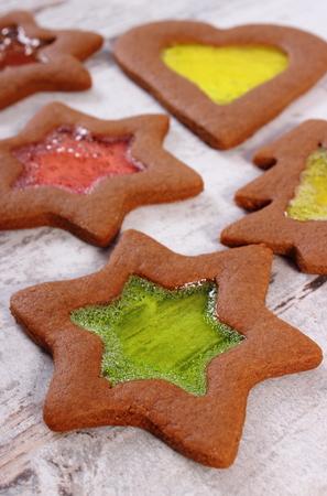 galletas de navidad: Pan de jengibre fresco decorado vitral hecho en casa, galletas de navidad en viejo fondo de madera blanco, tiempo de Navidad