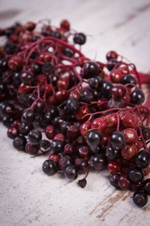 rustic food: Bunch of fresh elderberry on old rustic wooden background, healthy food, nutrition and alternative medicine
