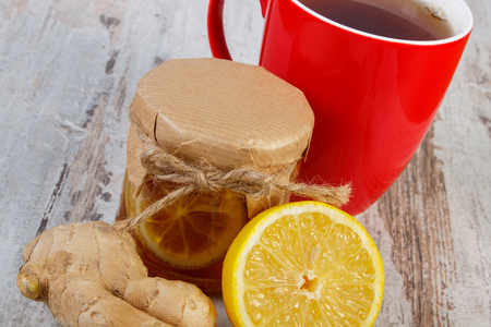 warming therapy: Lemon with honey in glass jar, fresh lemon, ginger and cup of hot tea on old wooden white table, healthy food, strengthening immunity and alternative therapy