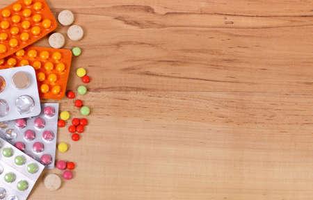 gripa: Medicamentos para el tratamiento de los resfriados, la gripe y nariz sobre fondo de madera