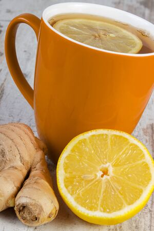 warming therapy: Fresh lemon, ginger and cup of hot tea with lemon on old wooden white table, healthy nutrition, strengthening immunity and alternative therapy