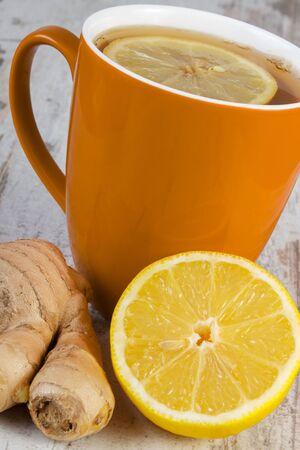 inmunidad: Lim�n fresco, jengibre y una taza de t� caliente con lim�n en la mesa de madera blanca, la nutrici�n saludable, fortalecer la inmunidad y la terapia alternativa