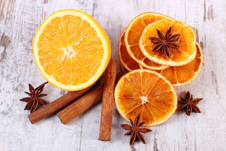 spices: Slices of dried and portion of fresh orange with spices for cooking or baking on old rustic wooden background, healthy food