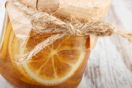 immunity: Lemon with honey in glass jar lying on old wooden white table, concept of healthy food, nutrition and strengthening immunity