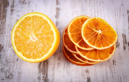 rustic food: Slices of dried and portion of fresh orange lying on old rustic wooden background, healthy food