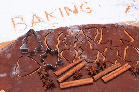 cookie cutters: Spice for baking, anise and cinnamon sticks, cookie cutters on dough for Christmas cookies and gingerbread, concept of baking and Christmas time
