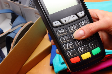 personal identification number: Use payment terminal for paying for purchases in store, enter personal identification number, credit card reader, clothes and laptop, finance concept