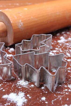 cookie cutters: Cookie cutters and rolling pin lying on dough for cookies and gingerbread, concept of baking and christmas time