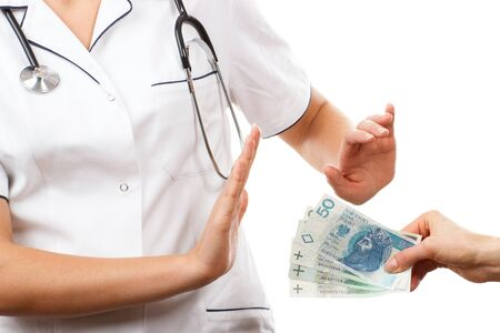 bribes: Woman doctor with stethoscope refusing bribes or kickbacks, polish currency money, patient giving money for medical services, concept of corruption Stock Photo