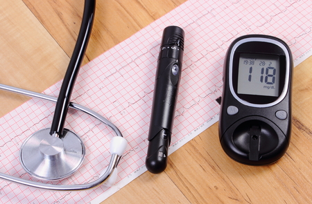 ecg monitoring: Glucose meter with lancet device and medical stethoscope lying on electrocardiogram graph, ecg heart rhythm, medicine and healthcare concept